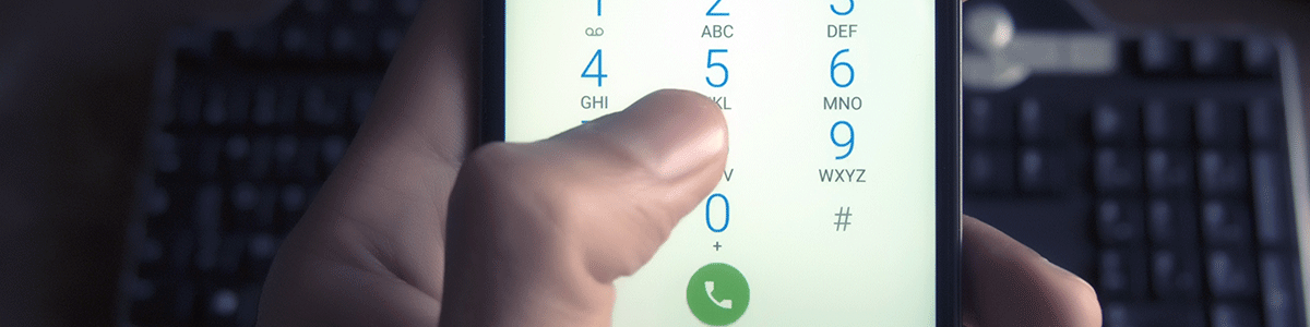 a person dials a number with a keyboard in the background